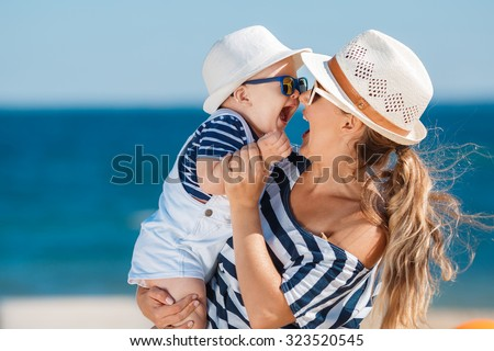 Happy family relaxing by the sea. Happy family resting at beach in summer. mother with baby boy resting on the beach. Young mother and her adorable little daughter on beach vacation - stock photo