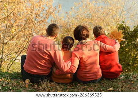 Happy family relaxing in autumn park back view - stock photo