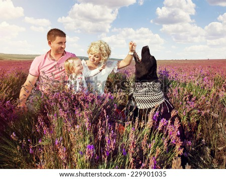 Happy family relaxing in nature lavender field. Mother, father, daughter and dog sitting in the grass. - stock photo