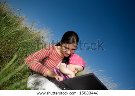 happy family relaxing on meadow with laptop - stock photo
