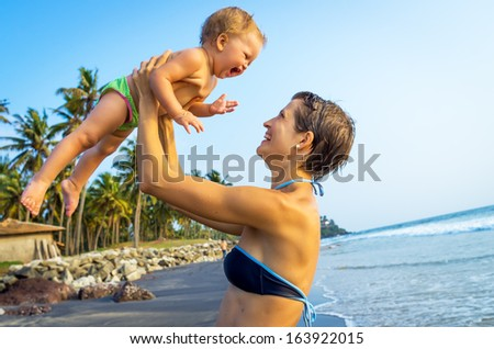 Happy family resting at tropical beach  - stock photo