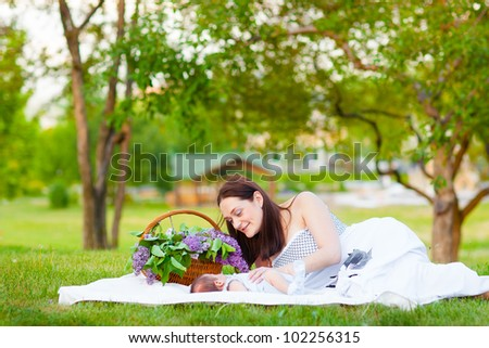 Happy family resting in summer park with lilac bouquet - stock photo