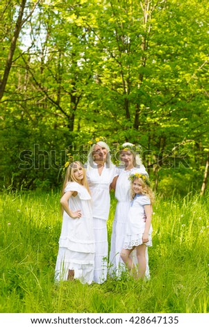 Happy family resting on the nature in the summer. Mom and daughter with wreath in the flowers in the park