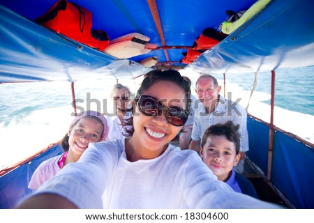 Happy family riding a fat boat going to an island. - stock photo