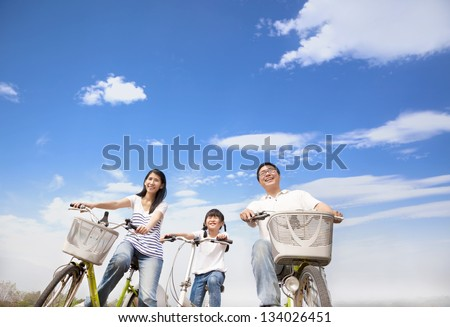 happy family riding bicycle with cloud background - stock photo