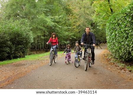 happy family riding bike in a park