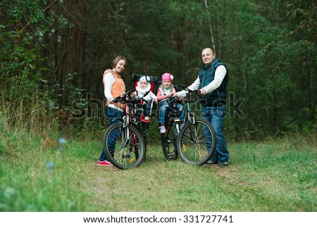 happy family riding bike in wood photo