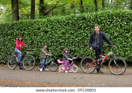 happy family riding bikes in a park - stock photo