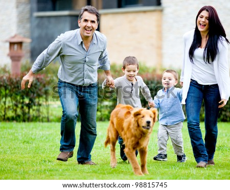 Happy family running at the backyard and having fun - stock photo