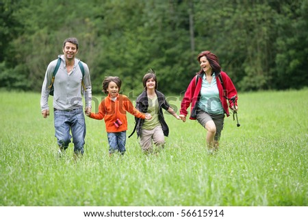 Happy family running in a field - stock photo