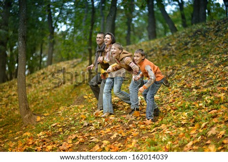 Happy family running in autumn park - stock photo