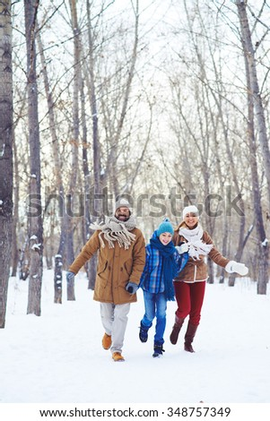Happy family running in snow in winter park - stock photo