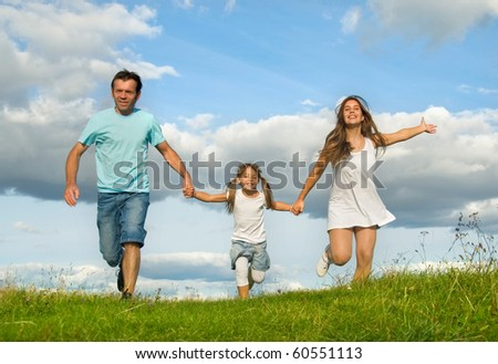 Happy family running on a hill - stock photo
