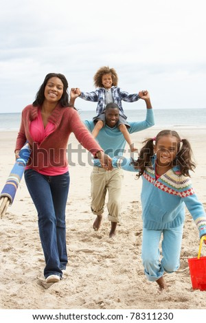 Happy family running on beach - stock photo