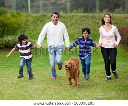 Happy family running outdoors chasing a dog - stock photo