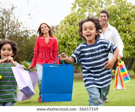 Happy family running outdoors with shopping bags - stock photo