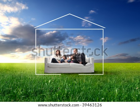 happy family seated on a couch in a grass field and surrounded by home drawing - stock photo