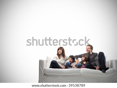 happy family seated on a couch with copy space - stock photo