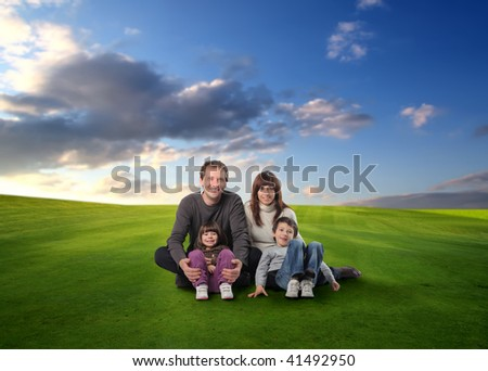 happy family seated on grass field - stock photo