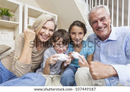 Happy family, senior adults & children, grandparents, grandson and granddaughter, having fun playing video console games together.