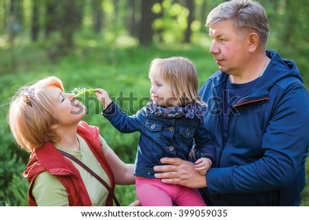 Happy family, senior couple with granddaughter, cute little girl - stock photo