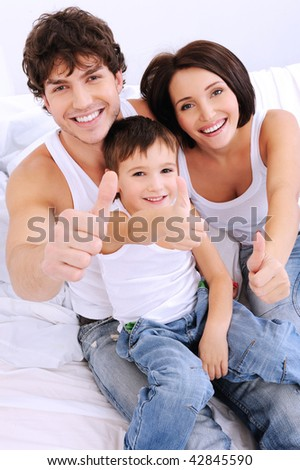 Happy family showing thumbs-up gesture. Portrait from high angle - stock photo
