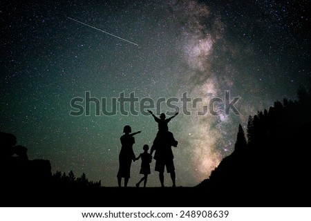 Happy family silhouette with Milky Way and beautiful night sky full of stars in background - stock photo