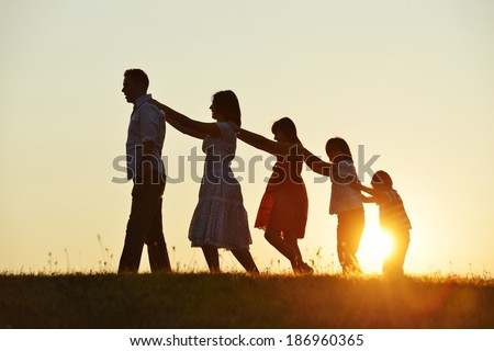 Happy family silhouettes on summer meadow