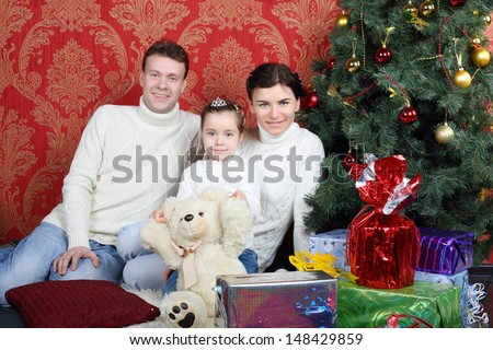 Happy family sit on floor with gifts near Christmas tree at home. - stock photo