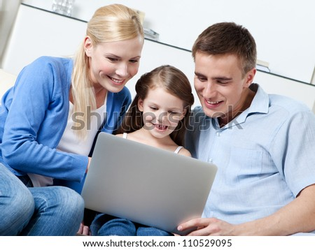 Happy family sit on the sofa with laptop - stock photo