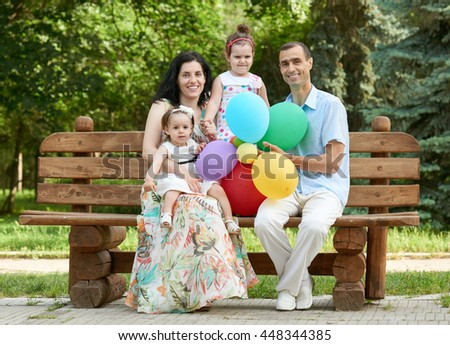 happy family sit on wooden bench in city park, summer season, child and parent , group of four people - stock photo