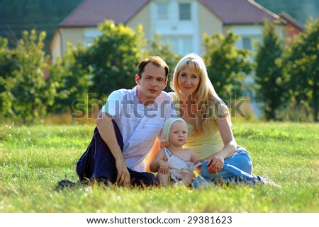 Happy family sits on meadow