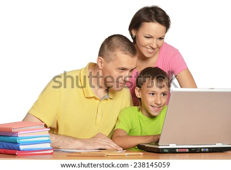 Happy family sitting at the table with laptop - stock photo