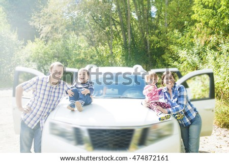 Happy Family sitting in hood of white big car looking in camera. Auto stand against green trees in park.
