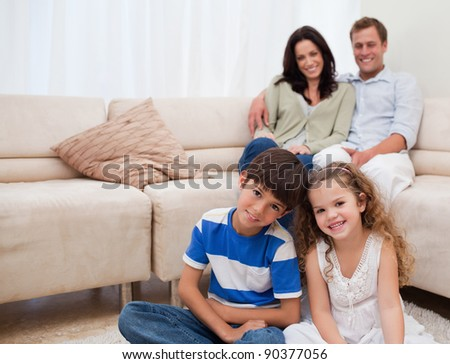 Happy family sitting in the living room - stock photo