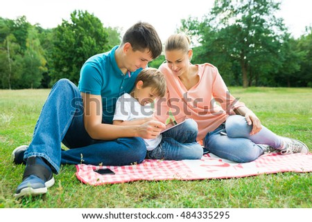 Happy Family Sitting In The Park Looking At The Digital Tablet