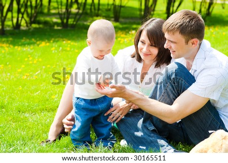 Happy family sitting in the summer park - stock photo