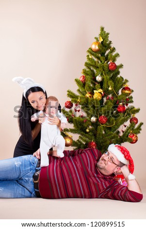 Happy family sitting near christmas pine