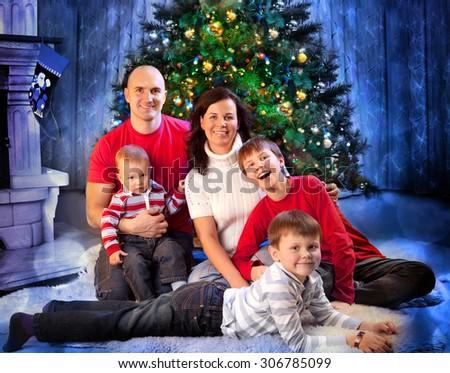 Happy Family Sitting Near Christmas Tree. - stock photo