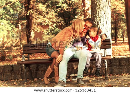 Happy family sitting on a bench sharing apple and enjoying the autumn day. - stock photo