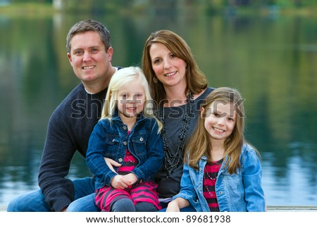 Happy Family sitting on a boat dock at a quiet lake.