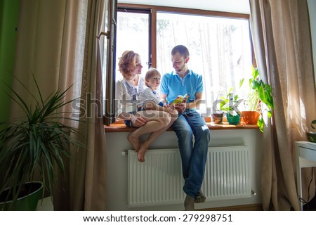 Happy family sitting on a window sill and read a book. - stock photo