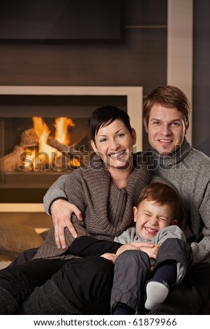 Happy family sitting on couch at home in a cold winter day, looking at camera, laughing. - stock photo