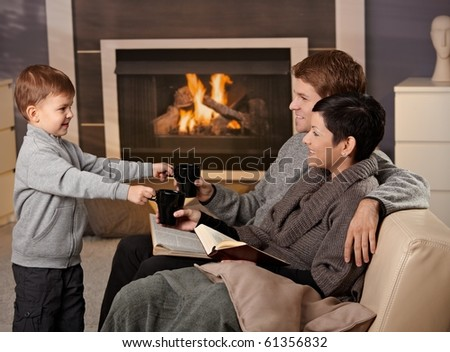 Happy family sitting on couch at home in front of fireplace, drinking tea, smiling. - stock photo