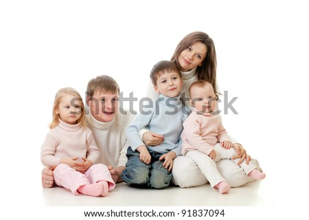 happy family sitting on floor and looking sideways on TV with great interest - stock photo