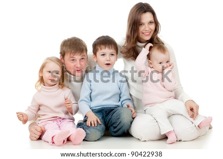 happy family sitting on floor and looking sideways (TV) with great interest - stock photo