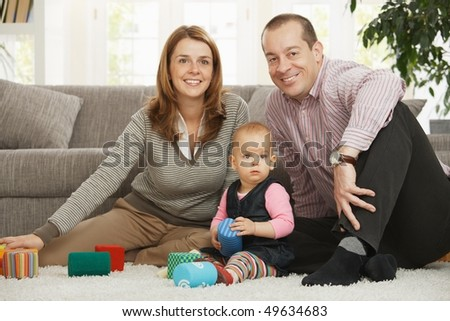 Happy family sitting on floor smiling at camera with baby girl.
