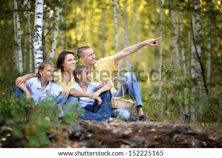Happy family sitting on grass in summer forest