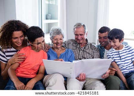 Happy family sitting on sofa and looking at photo album in living room - stock photo