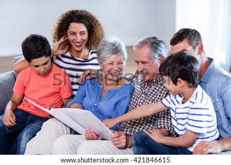 Happy family sitting on sofa and looking at photo album in living room